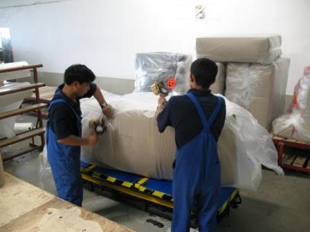 Nepali Uphosleters packing sofas at furniture Helvetica furniture factory in Poland